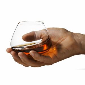 Holding a brandy bowl.